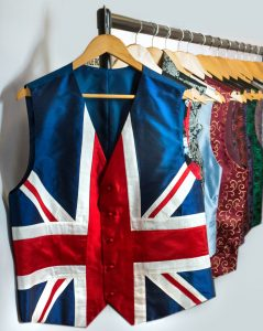 Waistcoats hanging in a row on a clothes rail.